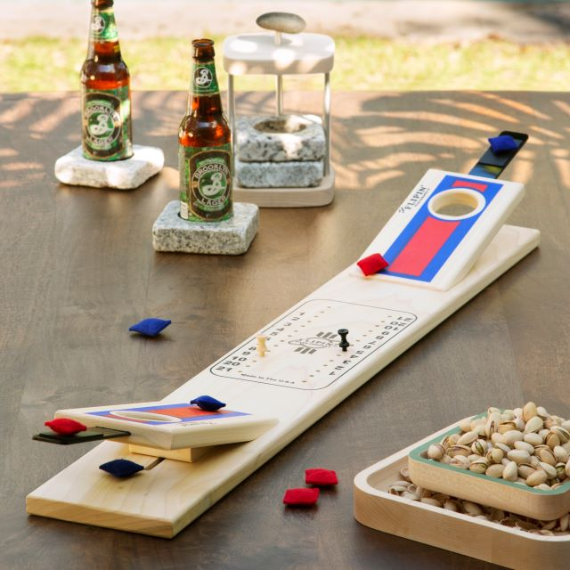 Tabletop cornhole game with stone coasters and a pistachio pedestal